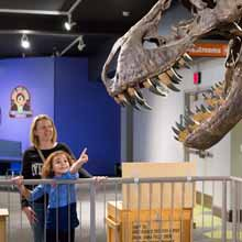 Girl pointing at T Rex Skeleton